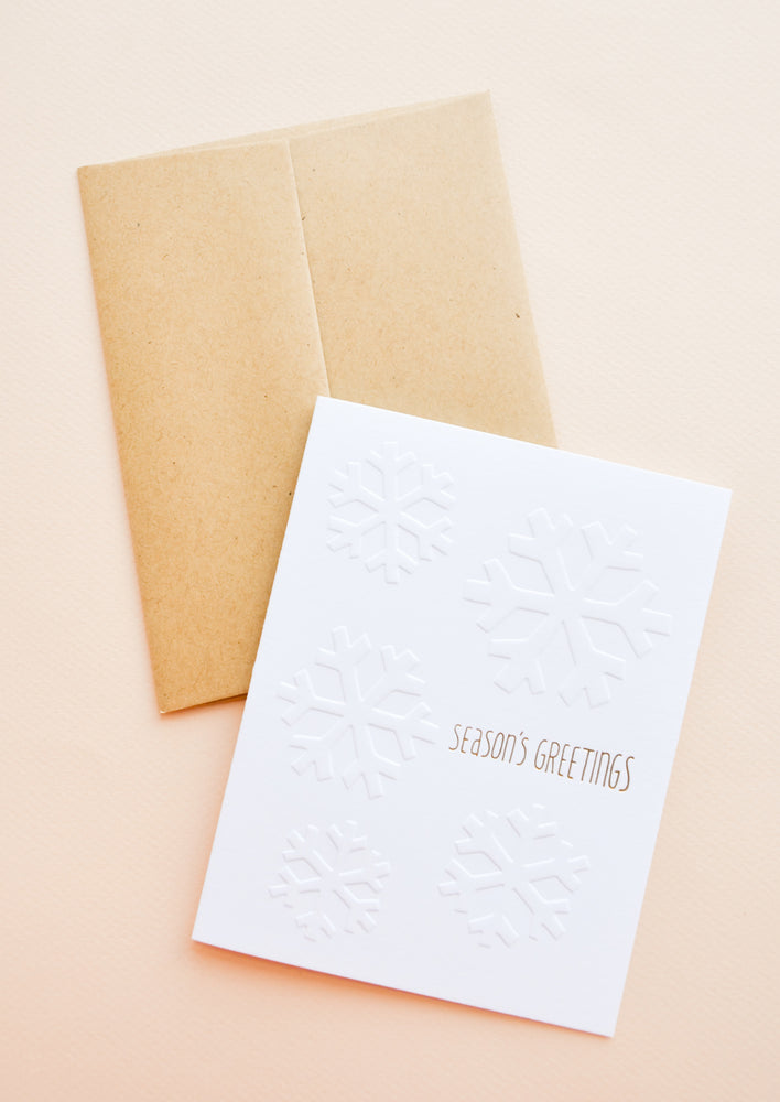"Brown envelope, White greeting card with ""Seasons Greetings"" written in gold foil."