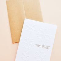 "1: Brown envelope, White greeting card with ""Seasons Greetings"" written in gold foil."