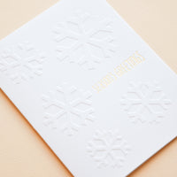 "2: White greeting card with ""Seasons Greetings"" written in gold foil."