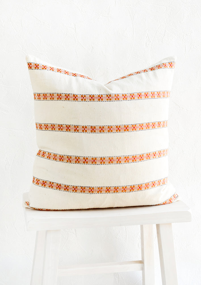 1: Square throw pillow with horizontal rows of geometric embroidered detailing.
