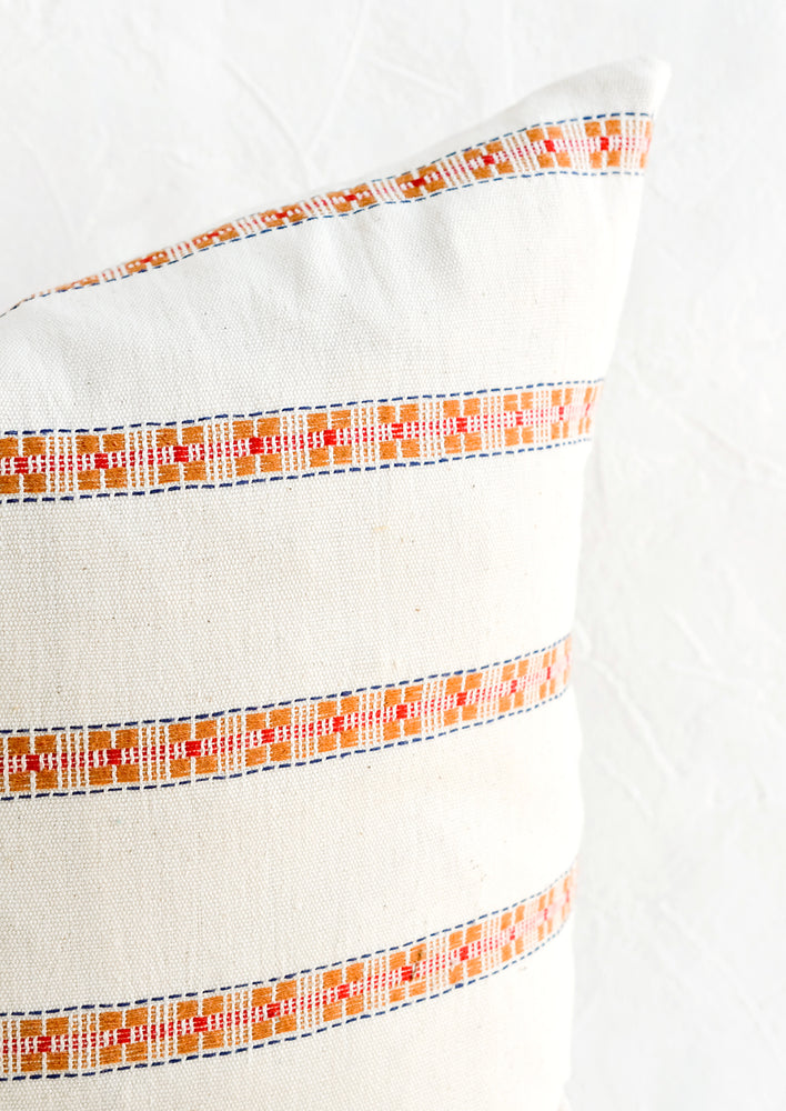 2: Intricate, geometric embroidery detailing on cotton throw pillow.