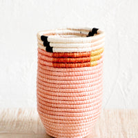 2: Pencil cup shaped woven sweetgrass basket in pink color combo with geometric trim, sitting on a table.