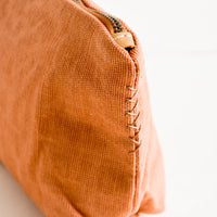6: X-shaped stitching detail on side of canvas makeup bag with leather detailing.