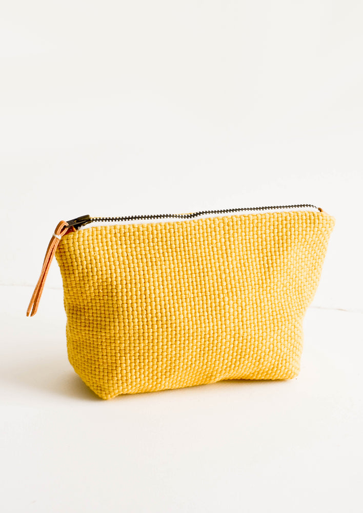 Cotton toiletry pouch in yellow, basketweave textured fabric. Zippered top with leather pull.