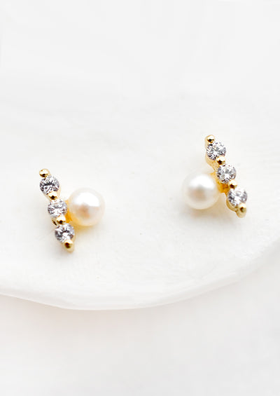 A pair of stud earrings with pearl aligned next to three crystal bar.