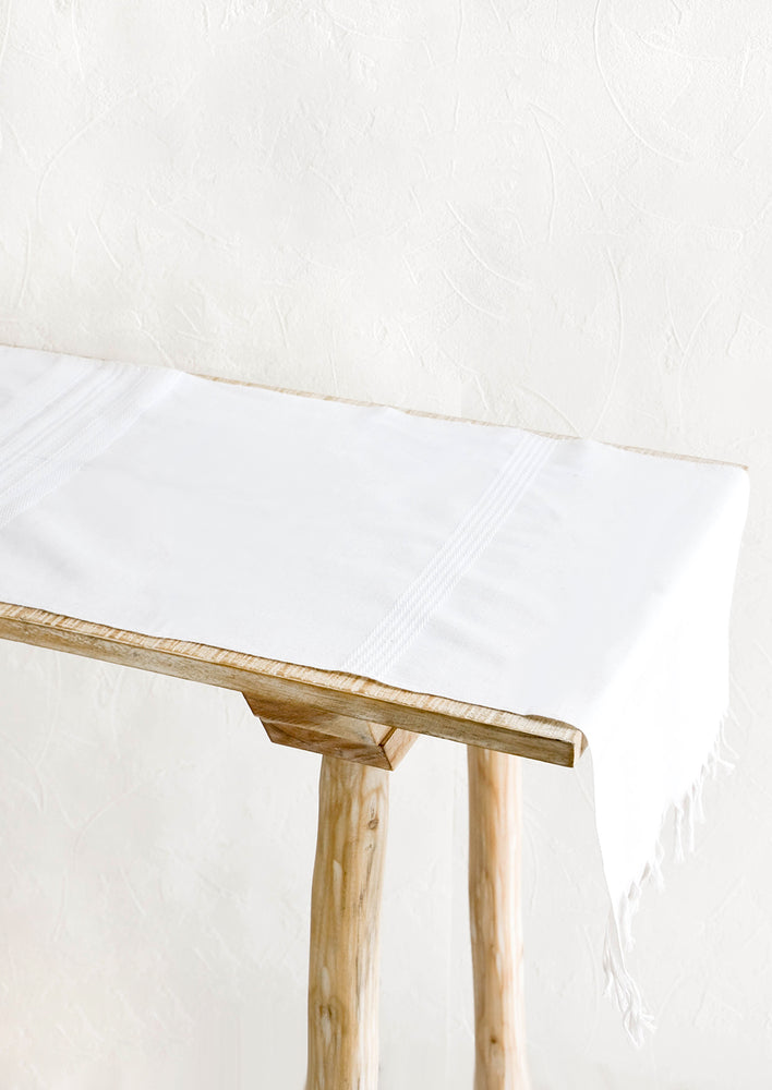 1: White table runner with tonal textured stripes, displayed on a wooden table