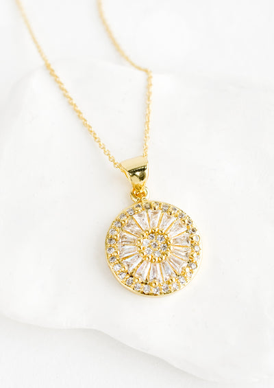 A gold necklace with round pendant encrusted with clear crystals.
