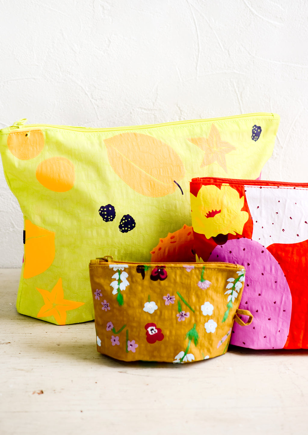 2: A set of three nylon pouches in different colors and patterns and incremental sizes.