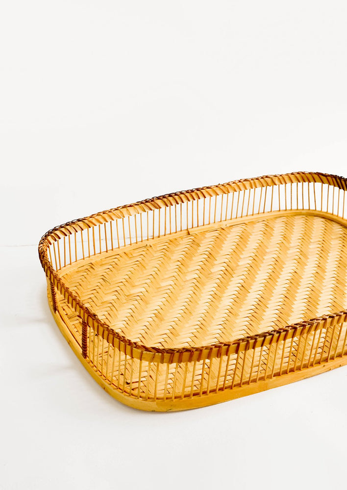 1: Rectangular serving tray with spoked rim and cutout handles at ends, made of natural bamboo
