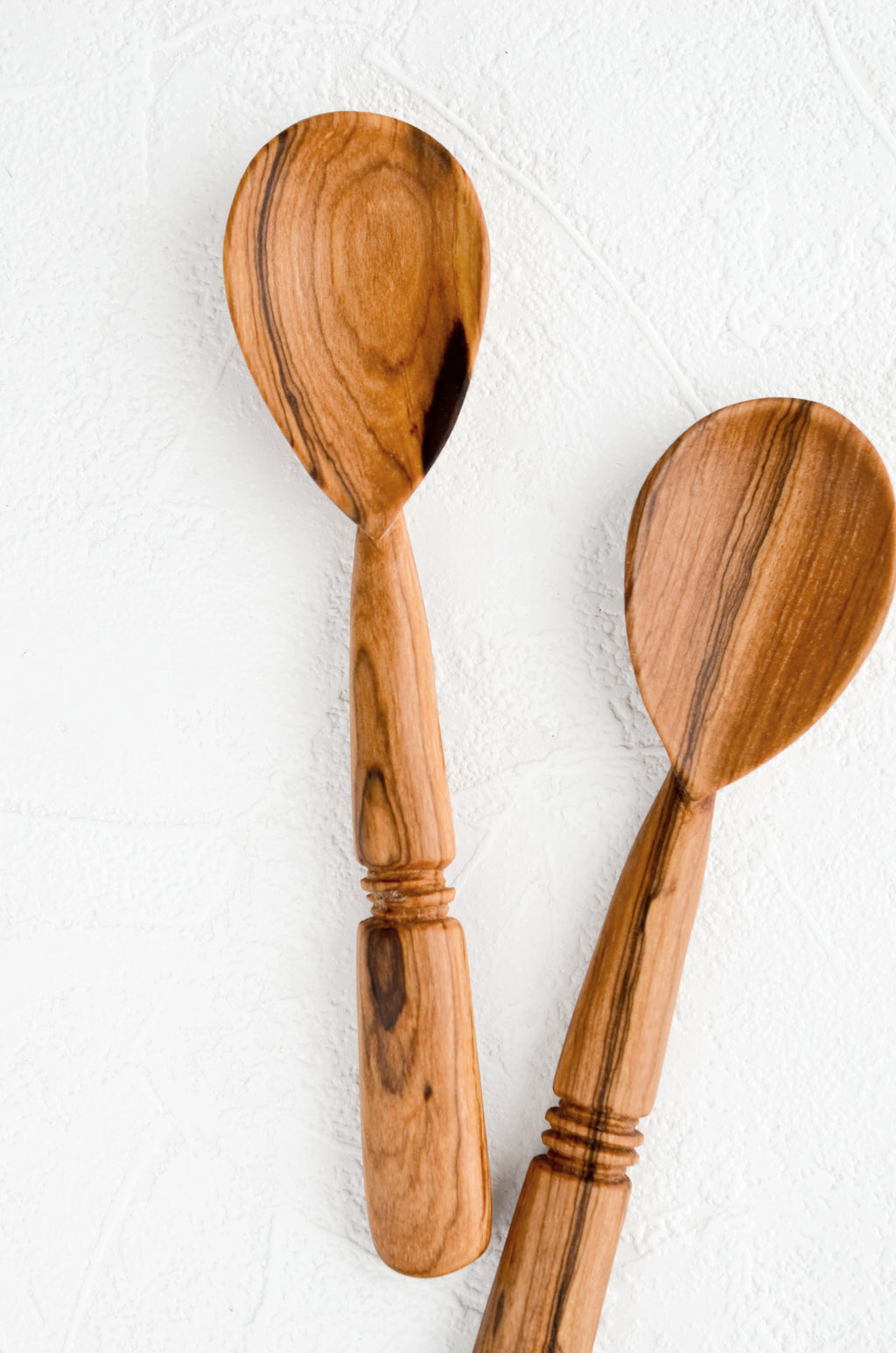 1: Two hand-carved spoons made from olivewood, each with its own unique grain pattern.