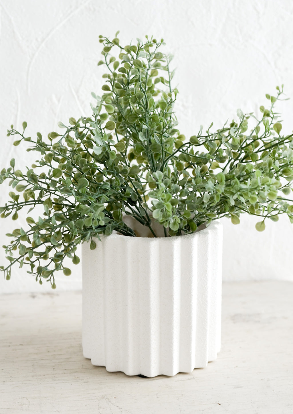 2: A geometric groove textured planter with plant.