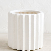 1: A matte white ceramic planter in grooved, geometric shape.