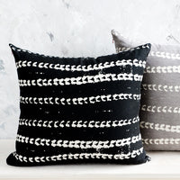 3: Two square throw pillows, one black and one grey, with white batik printed stripes.