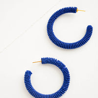 Lapis: Thick hoop earrings of lapis colored glass beads.
