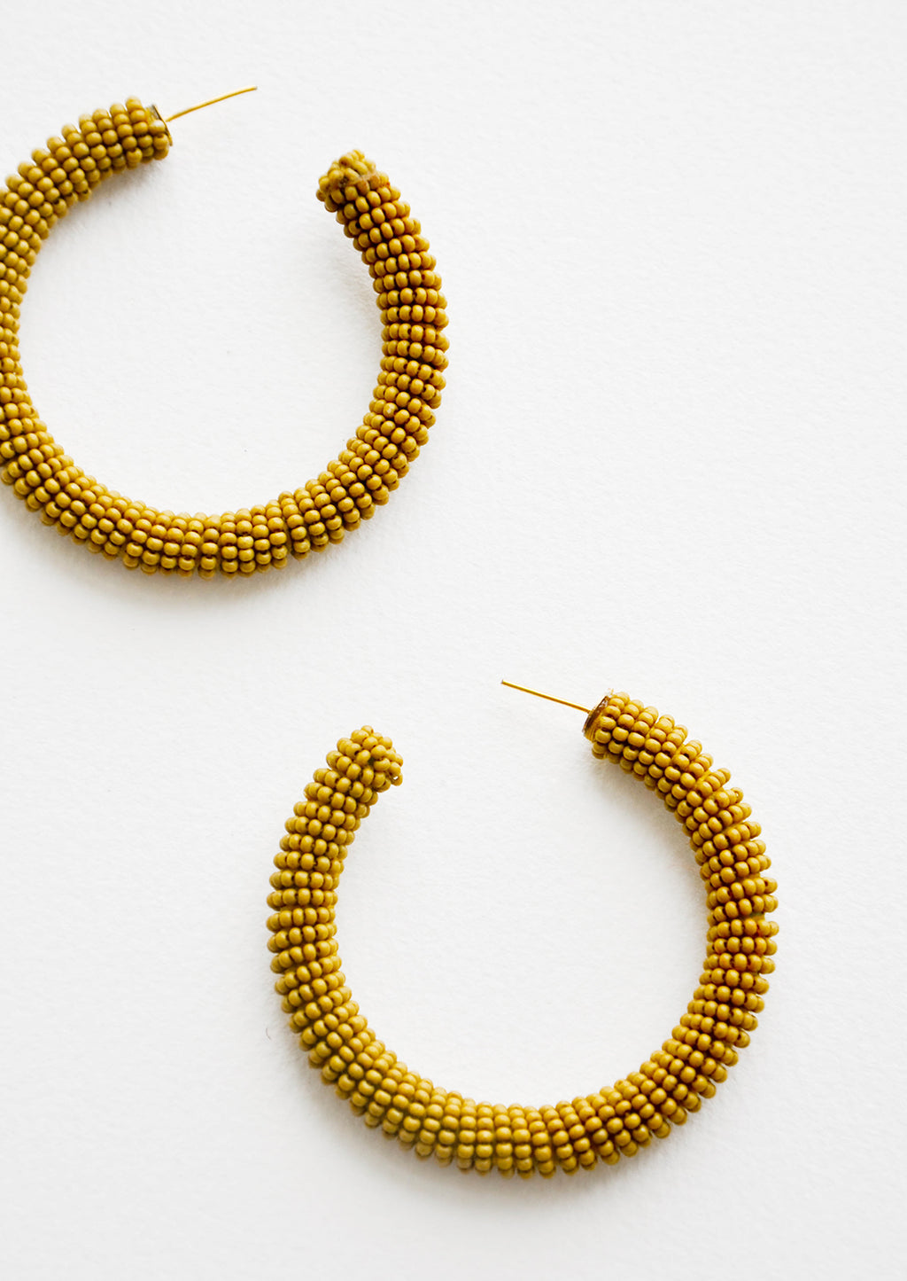 Lichen: Thick hoop earrings of yellow-green colored glass beads.