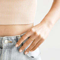 2: Model shot showing hand in front pocket wearing several gold rings.