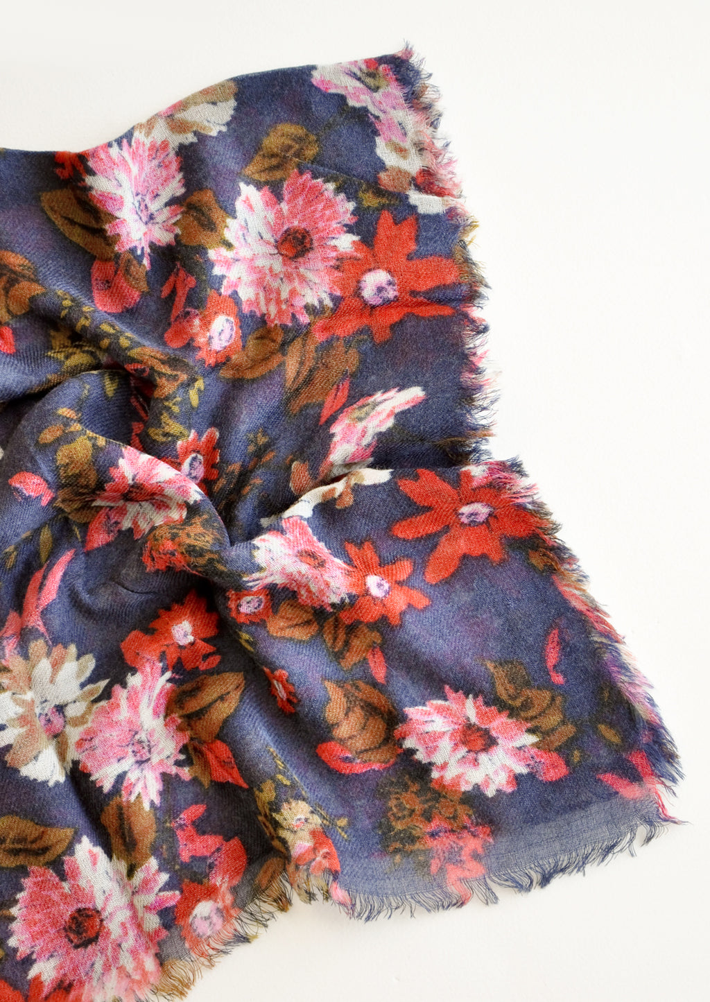 2: Close up shot of scarf with dark blue background and multi-colored pink and red floral pattern