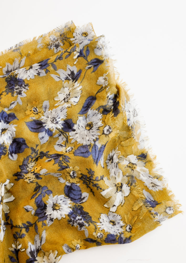 Green Ochre: Close up shot of scarf with dark yellow background and multi-colored blue and white floral pattern
