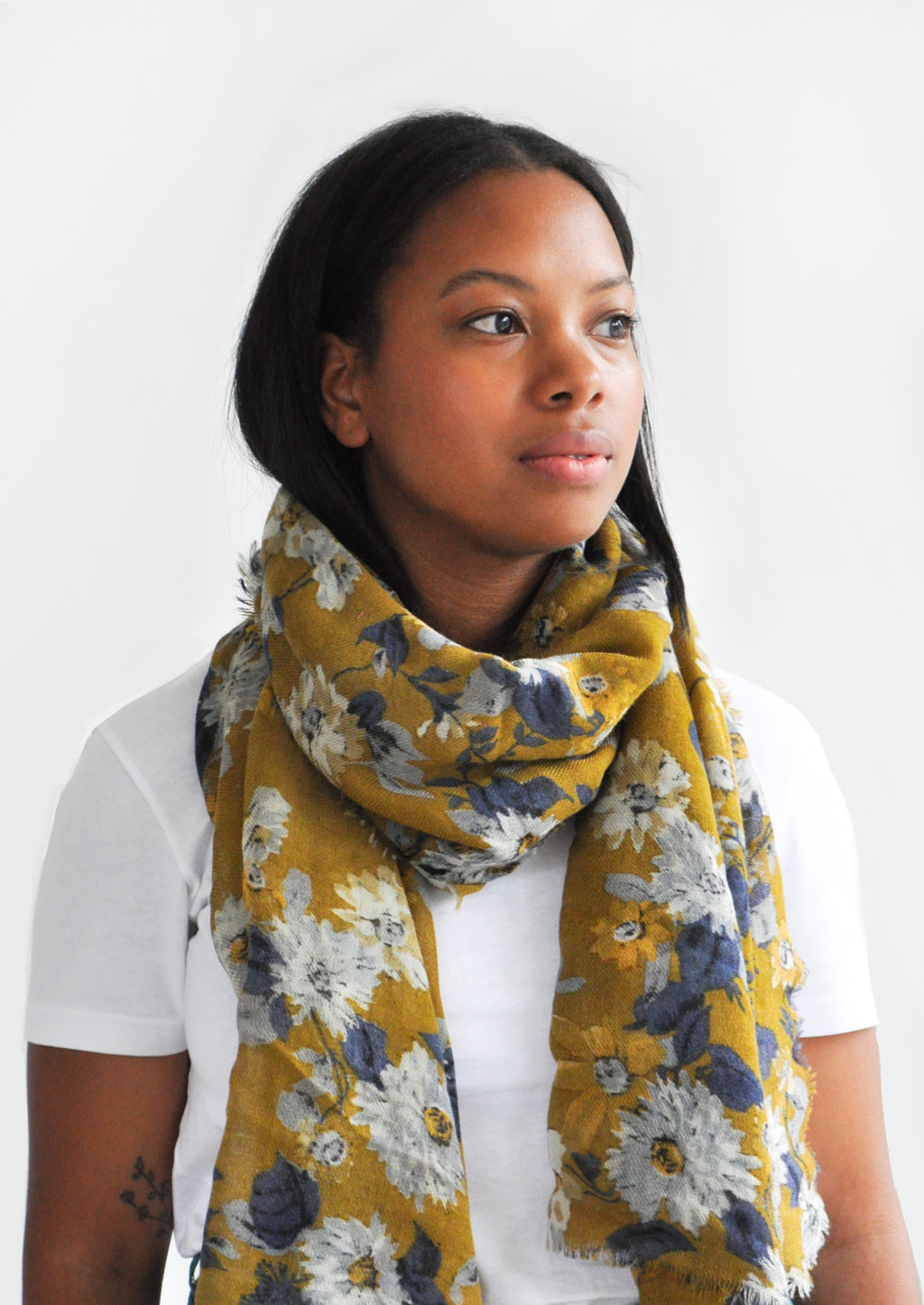 4: Product shot of woman wearing scarf and white top.