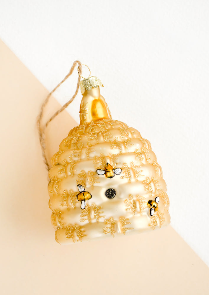 1: A glass ornament in the shape of a beehive with painted on bees.