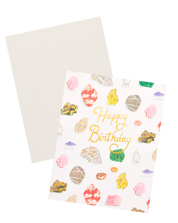 "3: Notecard with colorful drawings of gems and minerals and the text ""Happy Birthday"" in gold foil, with white envelope."