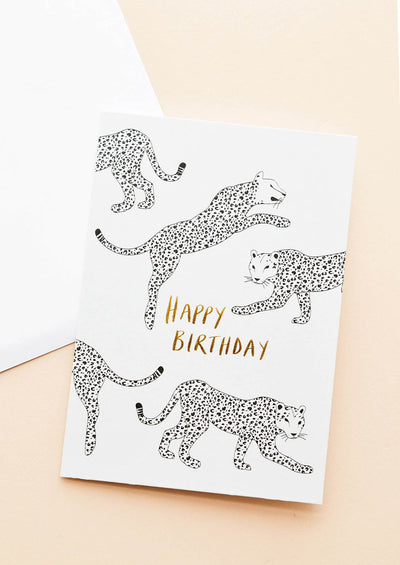 "A white greeting card patterned with black leopard illustrations and the phrase ""happy birthday"" in gold foil."