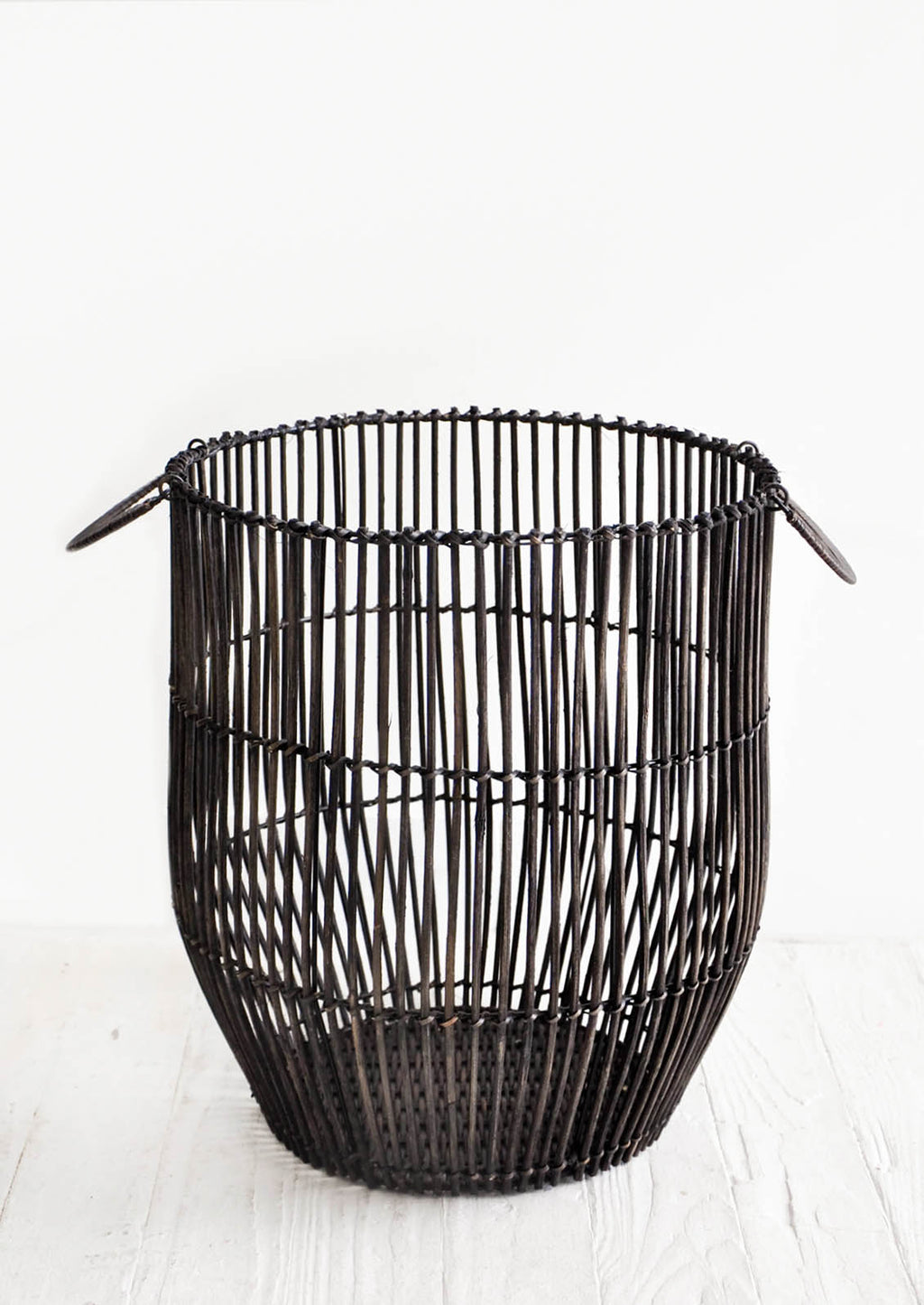 1: Round storage basket made from blackened rattan reeds with handles at sides