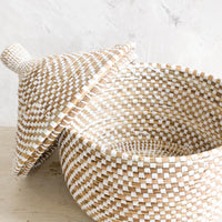1: Woven storage basket made from natural grass with white checkered pattern