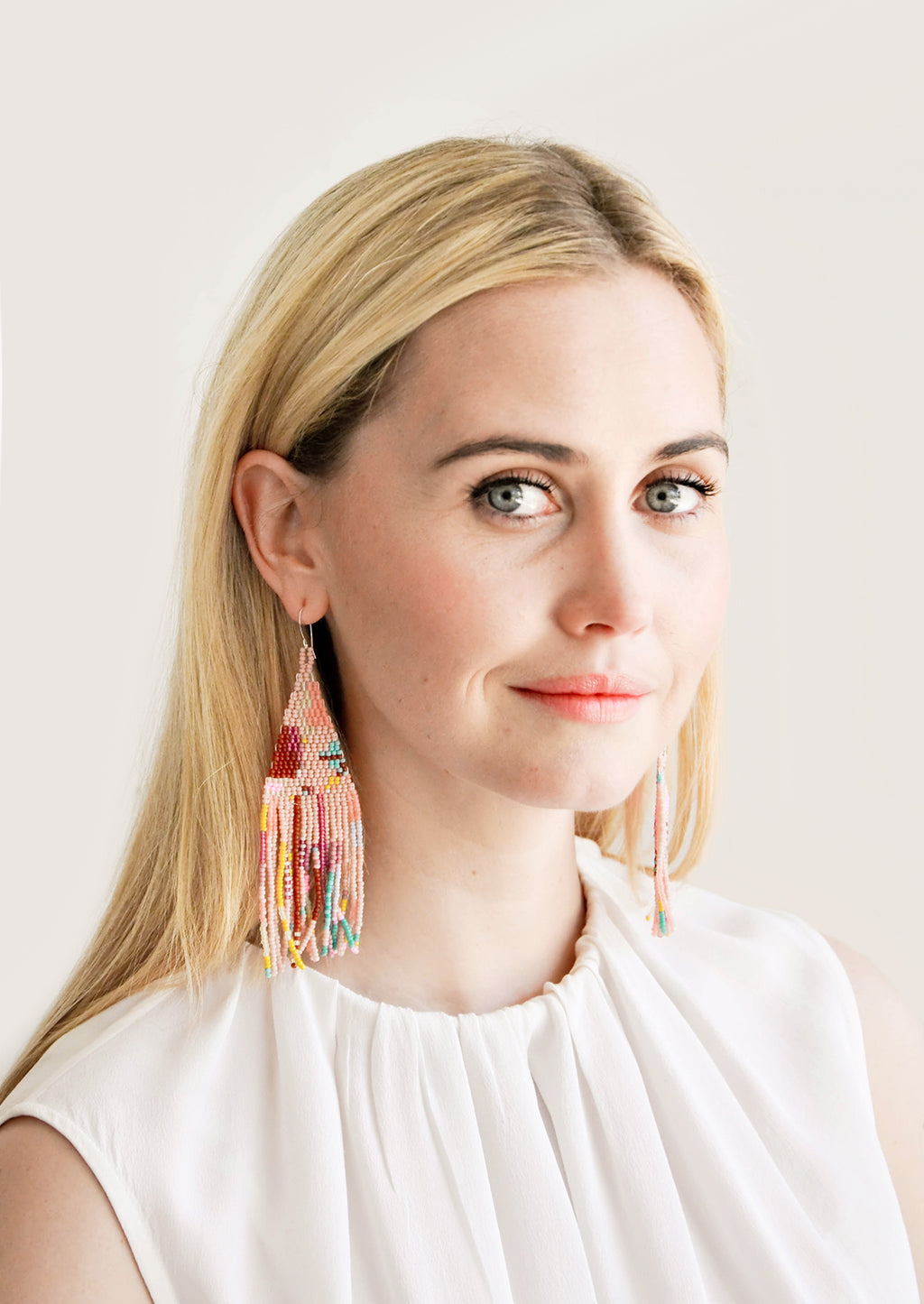 2: Model wears multicolored fringe beaded earrings and white blouse.