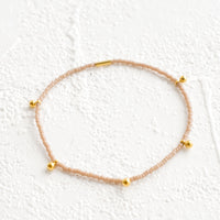Chai: Bracelet made from tan colored glass seed beads with brass ball accent charms and logo tag