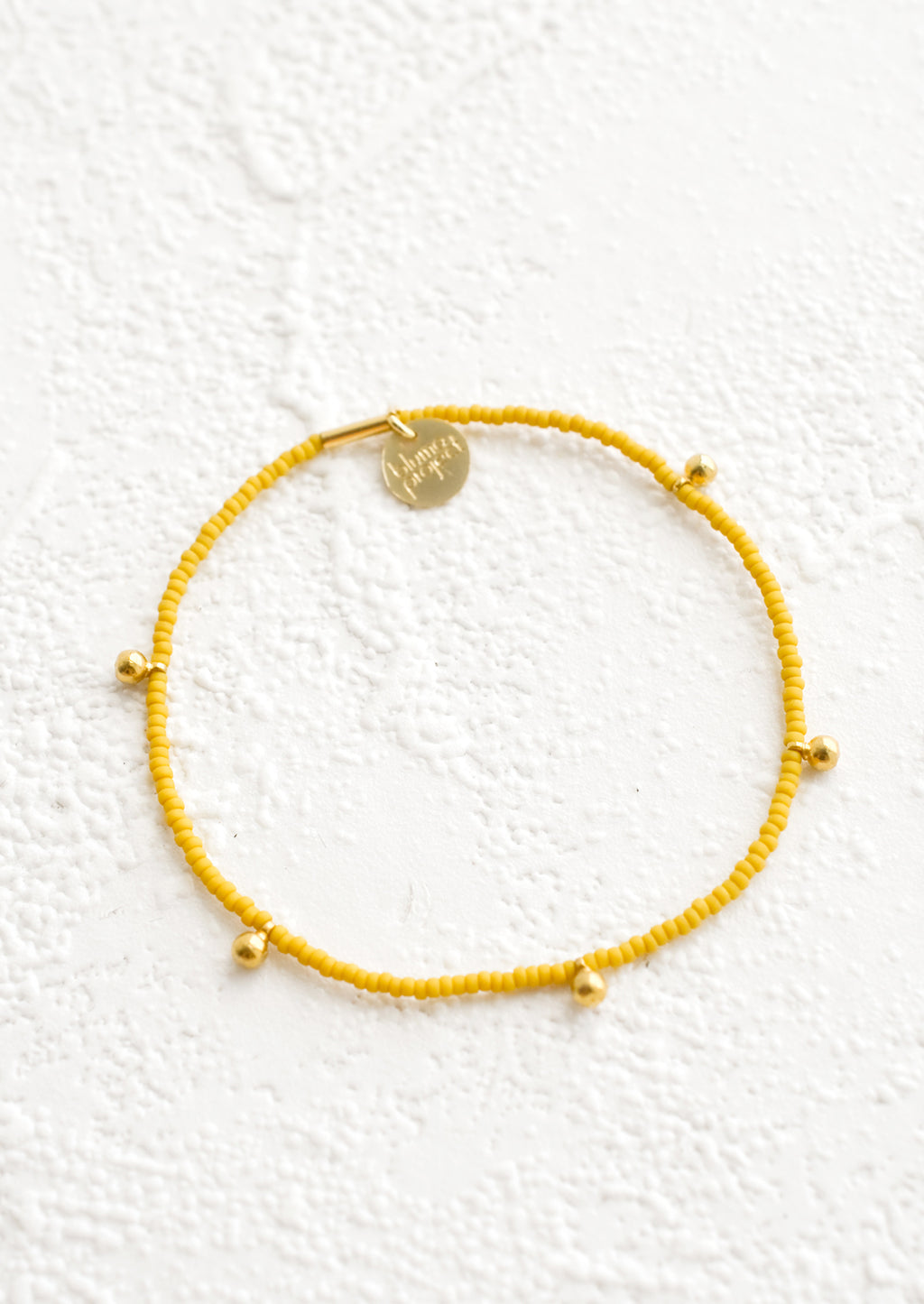Mustard: Bracelet made from mustard colored glass seed beads with brass ball accent charms and logo tag