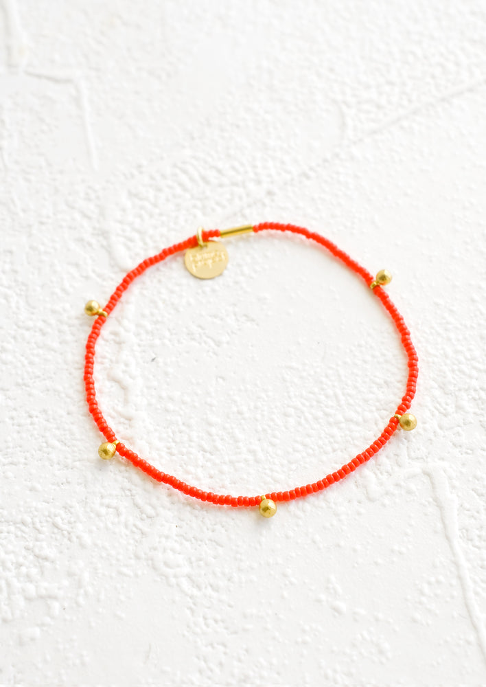Poppy: Bracelet made from red colored glass seed beads with brass ball accent charms and logo tag