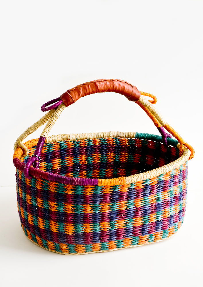 1: Woven basket made from multicolor dyed elephant grass with leather wrapped carrying handle