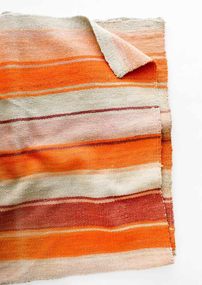 3: Woven textile intended for use as a rug or blanket, variegated colorful striped pattern.