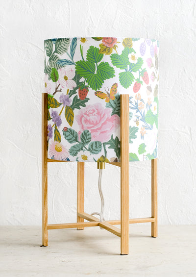 A table lamp with minimal oak base and botanical print shade.