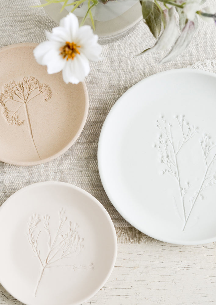 2: Stacked pastel porcelain plates with plant imprint designs.