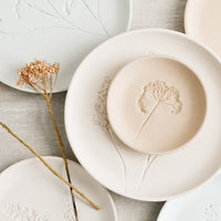 1: Stacked pastel porcelain plates with plant imprint designs.