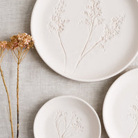 Small / Blush: Stacked pastel porcelain plates with plant imprint designs.