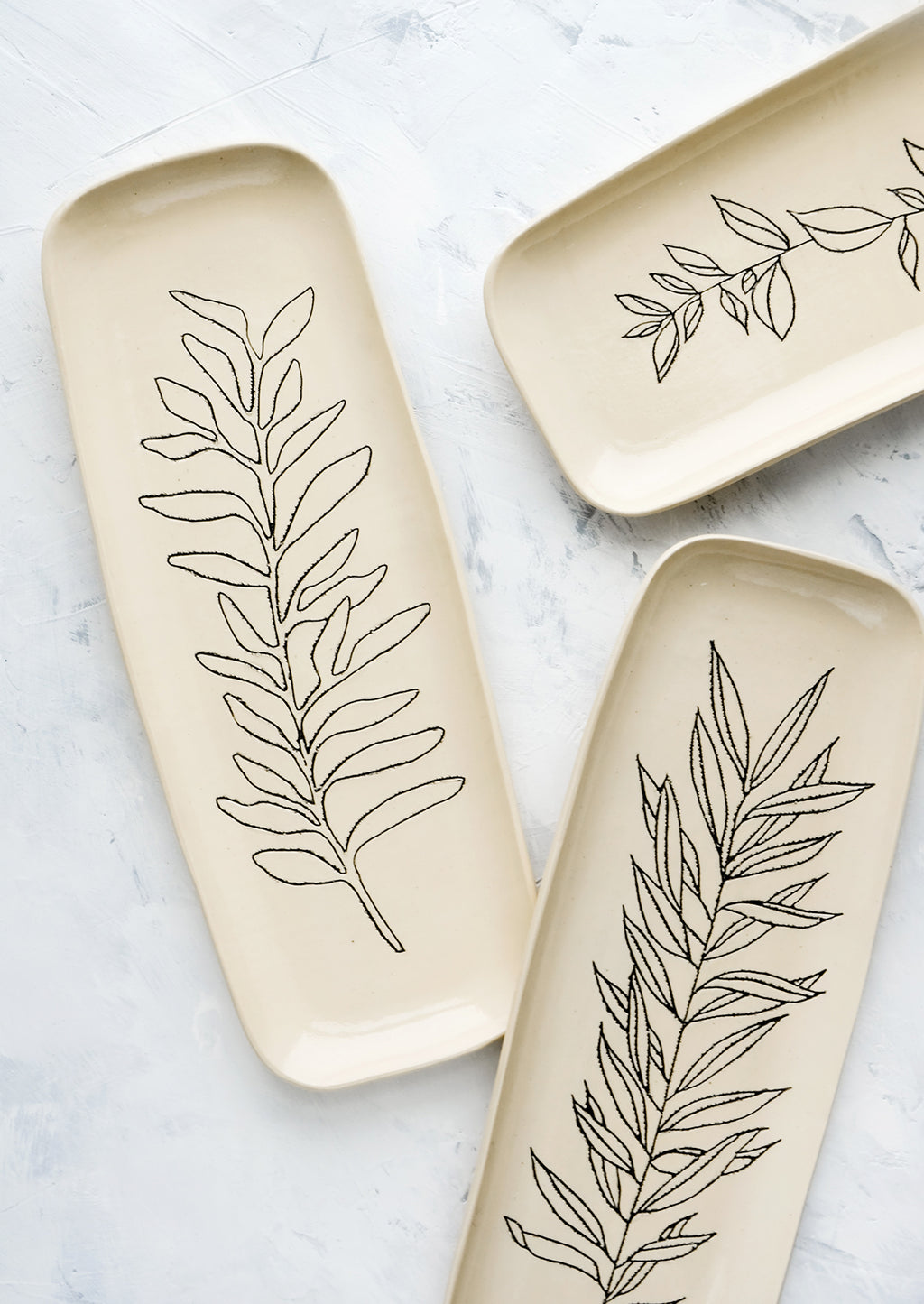3: Tall and slender ceramic platters in natural bisque color with etched black botanical drawings