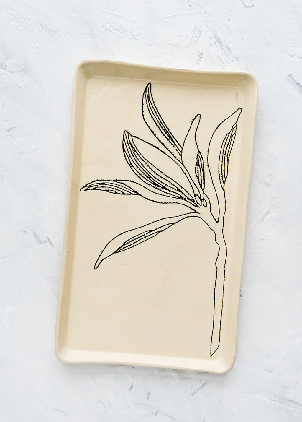 Magnolia: A rectangular ceramic tray in natural bisque color with an etched black drawing of a Magnolia branch.