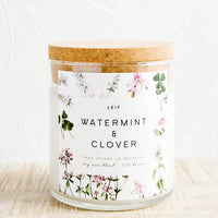"Watermint & Clover: A glass candle with a cork lid and white botanical printed label reading ""watermint and clover""."