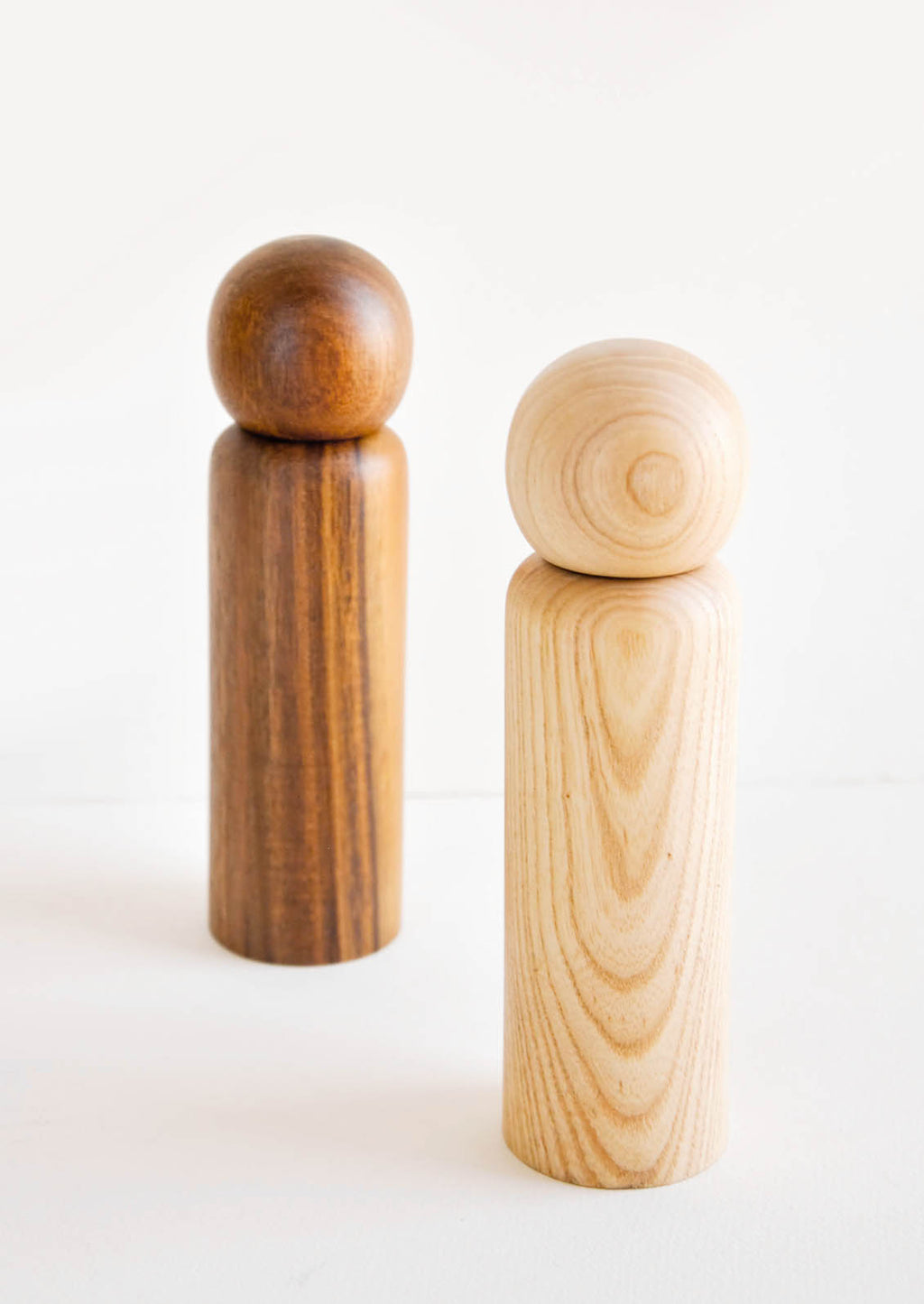 1: Two minimal Wooden Salt & Pepper Grinders with Spherical Tops in dark and light wood.