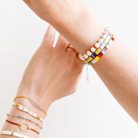 2: A woman's hands crossed with her wrists featuring many different bracelets.