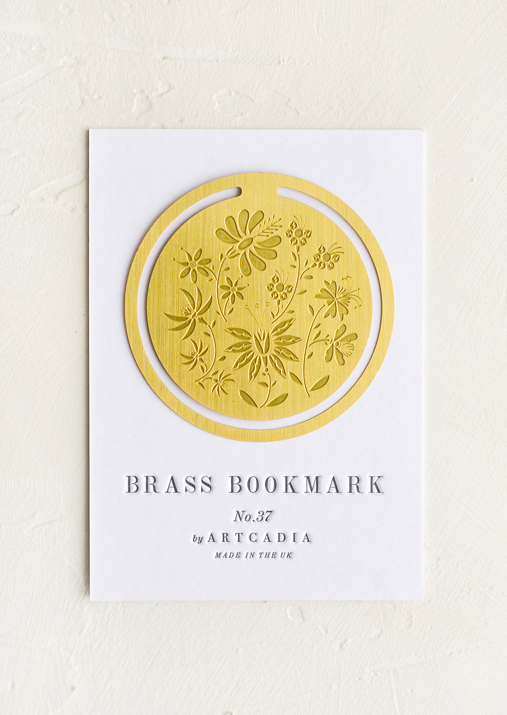 1: A circular brass bookmark with etched botanical pattern.