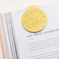 2: A circular brass bookmark with etched botanical pattern, marking a recipe page.