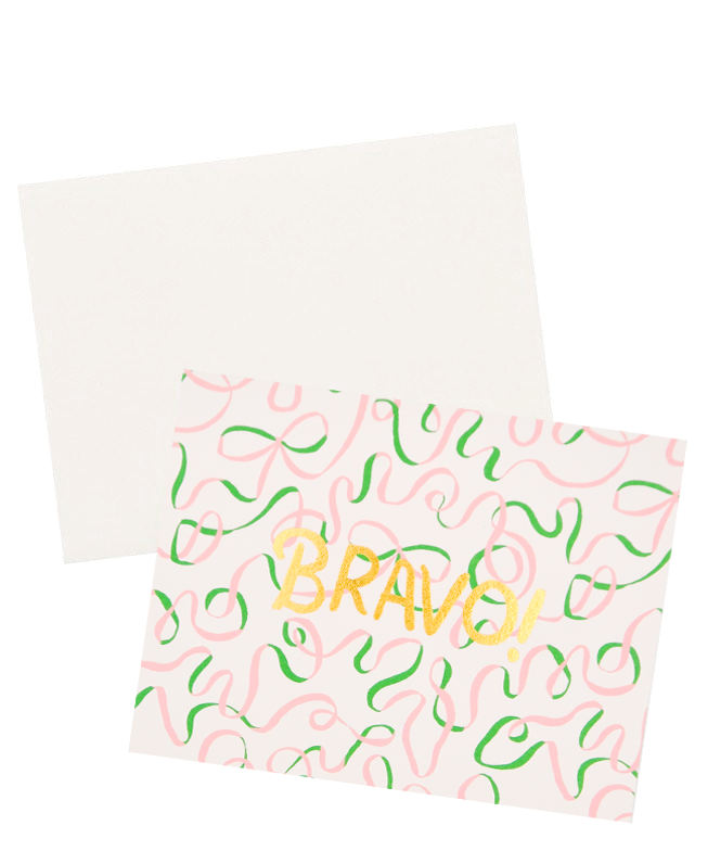 "3: A white envelope with a beige card patterned with illustrated green and pink ribbons and the word ""bravo"" in gold foil."