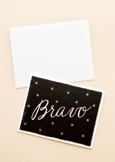"Notecard with gold dots on black background and the text ""Bravo"" in large script, with white envelope."