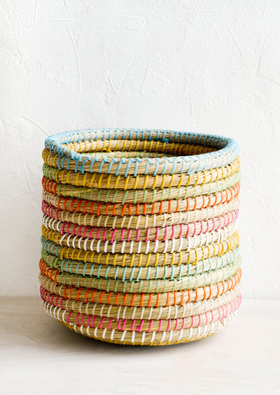 Woven seagrass storage basket with colored stripes comprised of woven plastic strips