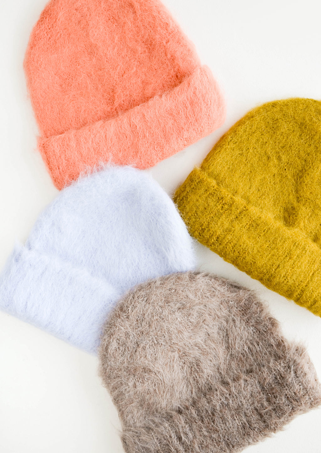 2: Four beanies in coral pink, pale blue, pale brown, and yellow-green laid out.