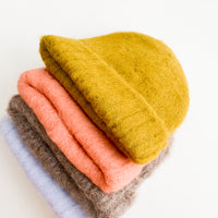 1: A neat pile of fuzzy beanies each of a different color.